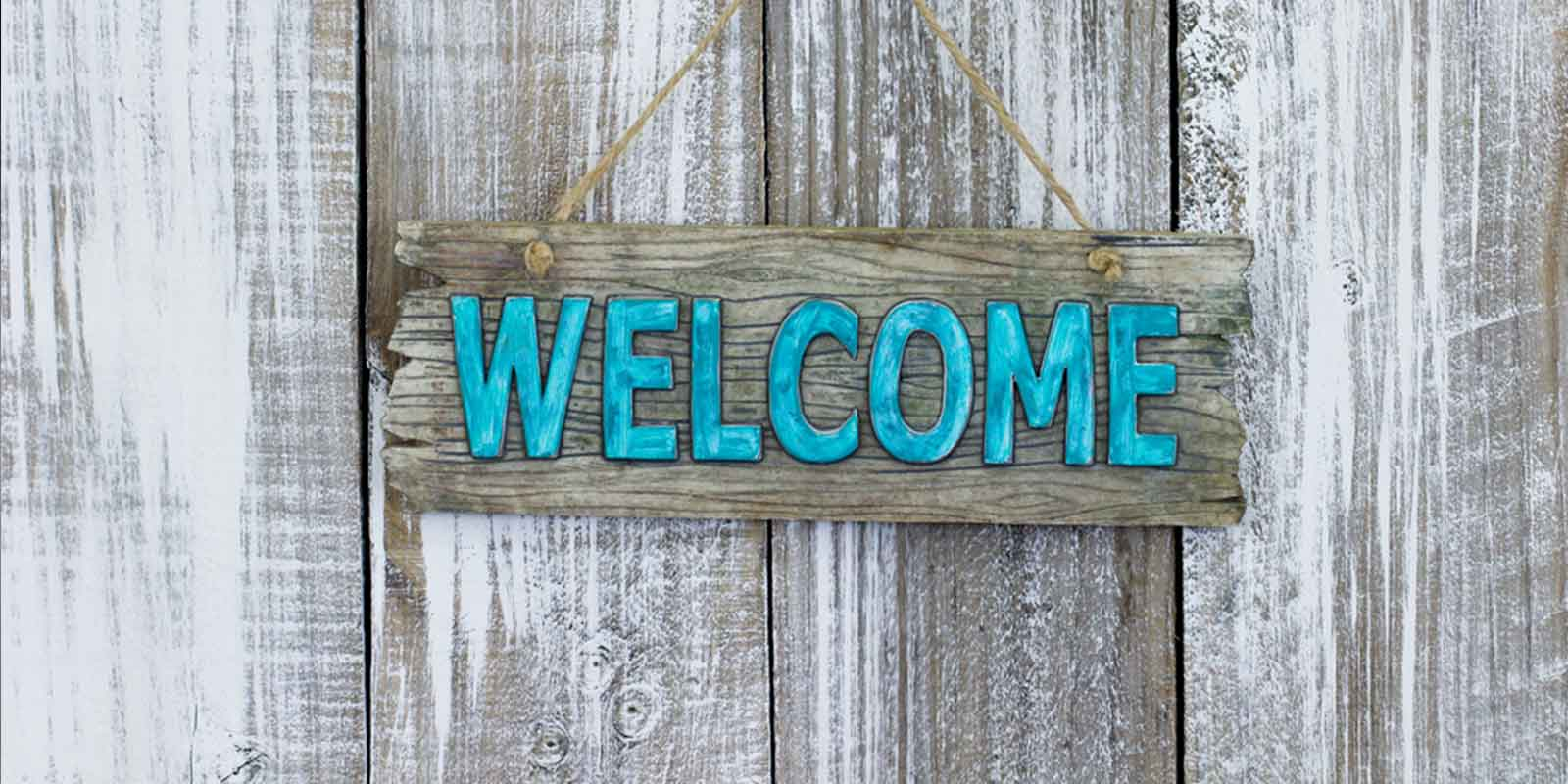 Wooden door with welcome sign inviting prospects into your business so you can fix your business.